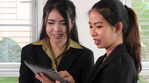 Two Attractive Asian Office Workers Use Tablet Footage
