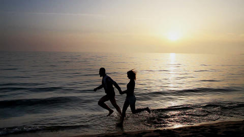 Loving couple running on the sea beach Stock Video Footage