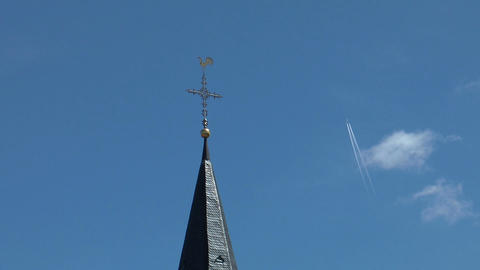Jet leaves contrails above weathercock Stock Video Footage