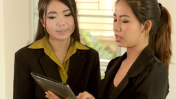 Two Asian Office Workers Explaining Work on a Tablet... Stock Video Footage
