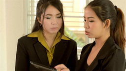 Two Asian Office Workers Explaining Work on a Tablet Computer Footage