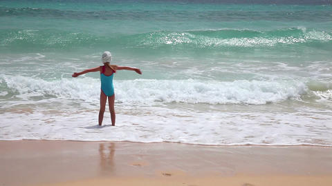 Young girl having fun with sea waves on the beach Stock Video Footage