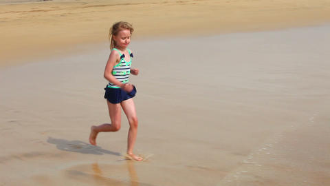 Cute young girl having fun with sea waves on the b Stock Video Footage