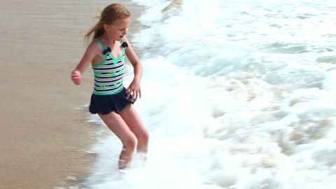 Cute young girl having fun with sea waves on the b Footage