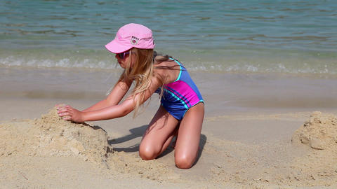 Young girl in swimsuit builds sand castle on beach Footage