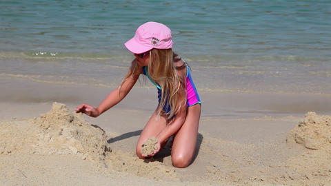 Young girl in swimsuit builds sand castle on beach Stock Video Footage