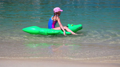 Girl playing at beach on crocodile in sea water Footage