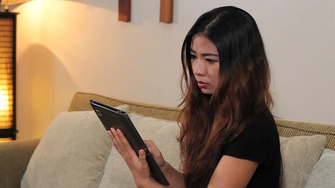 Attractive Asian Woman Using Tablet In Living Room Stock Video Footage