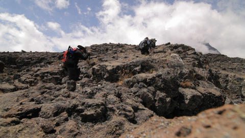 Trekkers stepping on to a rocky outcrop Footage