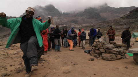 Porters dance at the base of the mountain Stock Video Footage
