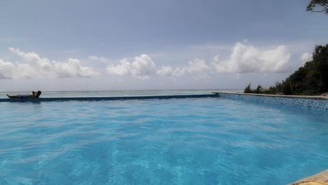 Resort pool seaside with man relaxing Stock Video Footage