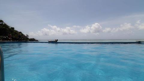 Resort pool seaside with man relaxing Footage
