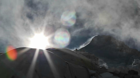Sun rising from behind tents and cloud Stock Video Footage