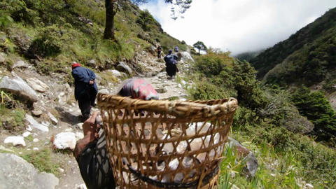 Porters headed up trail Stock Video Footage
