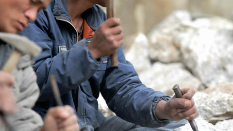 Stonemasons chiseling away rock Stock Video Footage