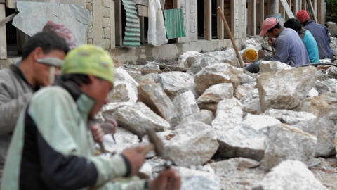 View of stone pile and masons chiseling Stock Video Footage