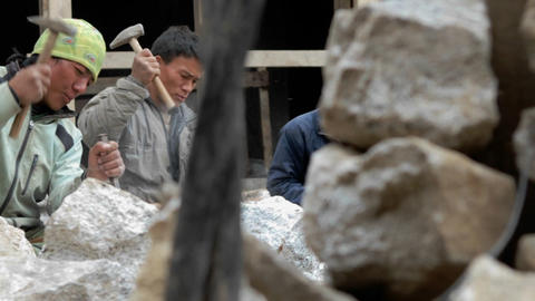 Slow pan of stone masons chiseling Stock Video Footage