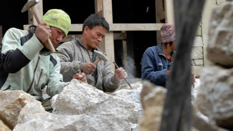 Slow pan of stone masons chiseling Footage