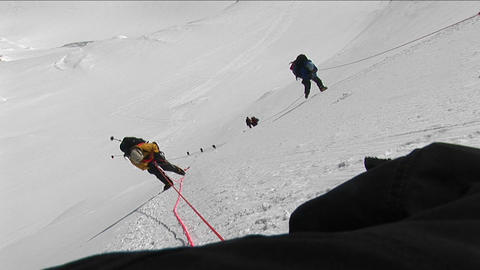Climbers climbing down steep slope Stock Video Footage