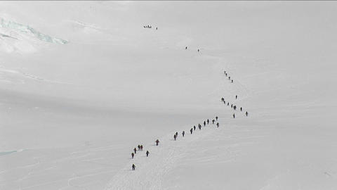 Lines of climbers on a steep slope of the mountain Stock Video Footage
