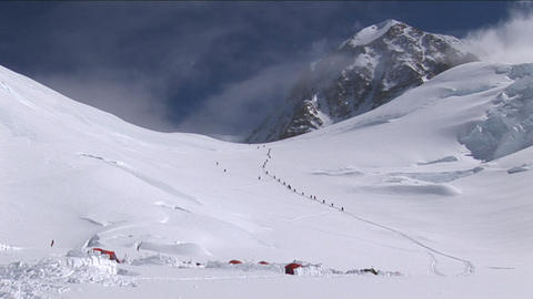 Line of climbers above camp Stock Video Footage