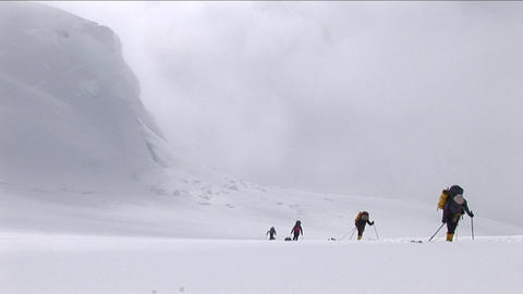 Climbers ascending with snow coming down Footage