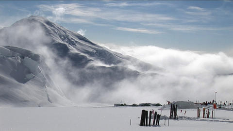 Skis in the snow as the wind blows over peak Stock Video Footage
