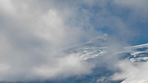 Clouds blow past a peak eventually cover it Stock Video Footage