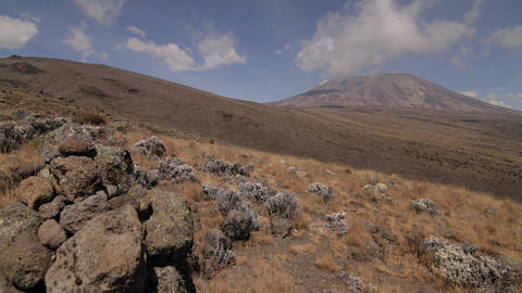 Kilimanjaro, clouds above, rocks in front Stock Video Footage