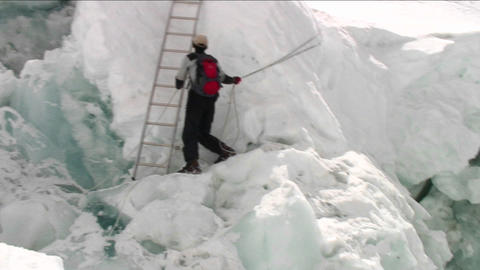 Pan from crevasse to Sherpa holding ropes Footage