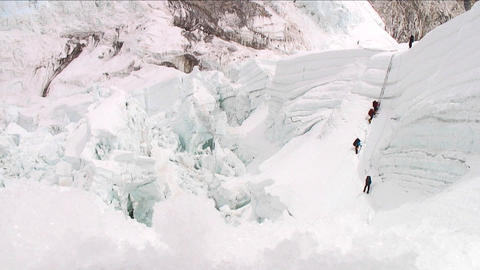 Climbers on large ladder at top of icefall Stock Video Footage