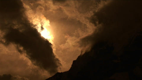 Pan onto peak with clouds and sunlight Stock Video Footage