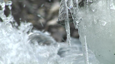 Water dripping off icicles, water rushing by Footage