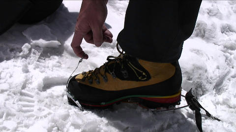 Putting crampons on boots Stock Video Footage