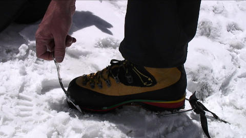 Putting crampons on boots Footage