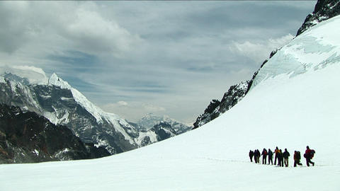 Climbers walking across snowy plateau Footage