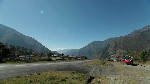 Helicopter beside runway at Lukla, plane takes off Stock Video Footage