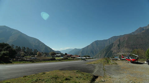 Helicopter beside runway at Lukla, plane takes off Footage