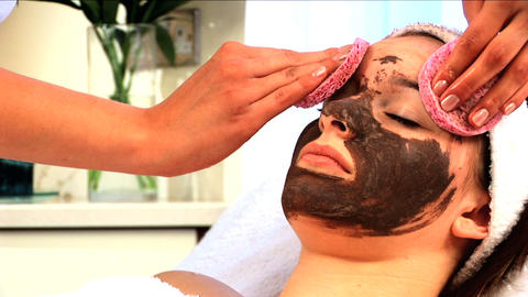 Young brunette girl having facial skin mask removed at... Stock Video Footage