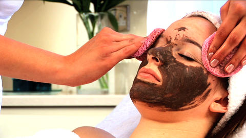 Young brunette girl having facial skin mask removed at health & beauty spa Footage