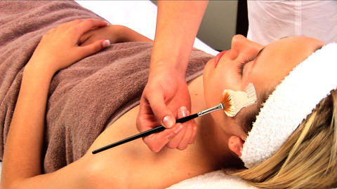 Young blonde girl having facial skin mask applied at beauty spa Footage