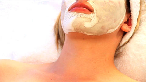 Young blonde girl resting with facial skin mask at beauty spa with candles in foreground Footage