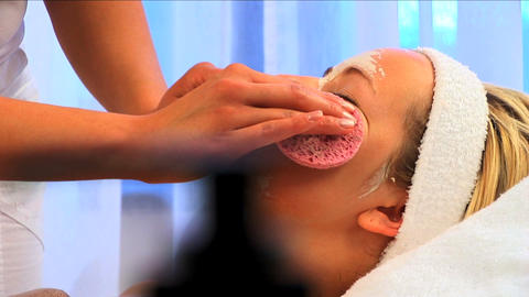 Young blonde girl having facial skin mask removed at health & beauty spa Footage