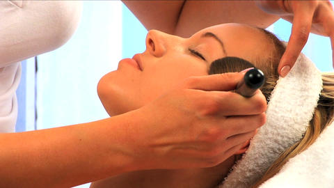 Beautiful blonde girl having cosmetics applied at beauty spa Stock Video Footage