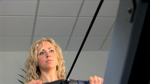 Beautiful blonde girl enjoys exercising at the gym Footage