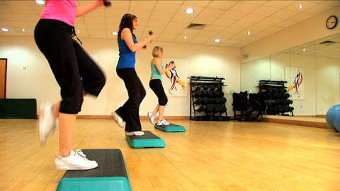 Beautiful young girls doing aerobic exercises at a gym Footage