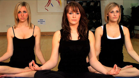Beautiful young girls doing yoga exercises at a gym Stock Video Footage