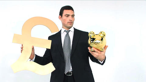 Businessman holding gold piggy bank and pound symbol... Stock Video Footage