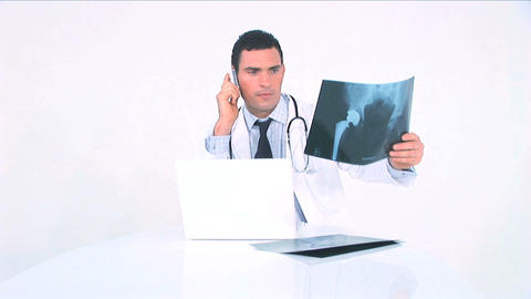 Doctor examining x-ray and consulting it on the phone Footage