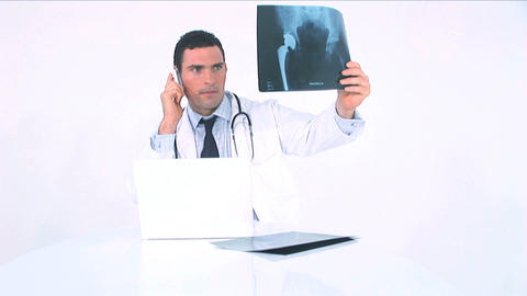 Doctor examining x-ray and consulting it on the phone Stock Video Footage